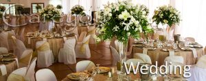 Indoors wedding reception venue with decor, selective focus on flowers